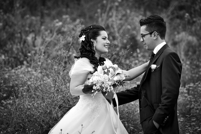 Couple holding bouquet while standing on field