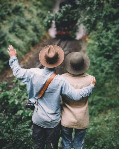 Rearview of couple looking at train in forest