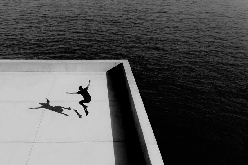 High angle view of man jumping on sea