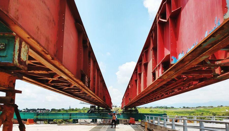 Male Worker Standing Below Bridge At Construction Site