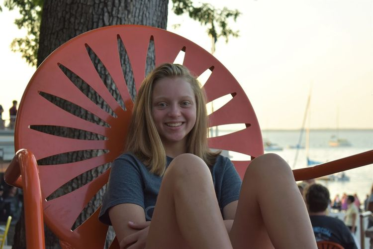 Portrait of smiling girl sitting on chair at beach against sky