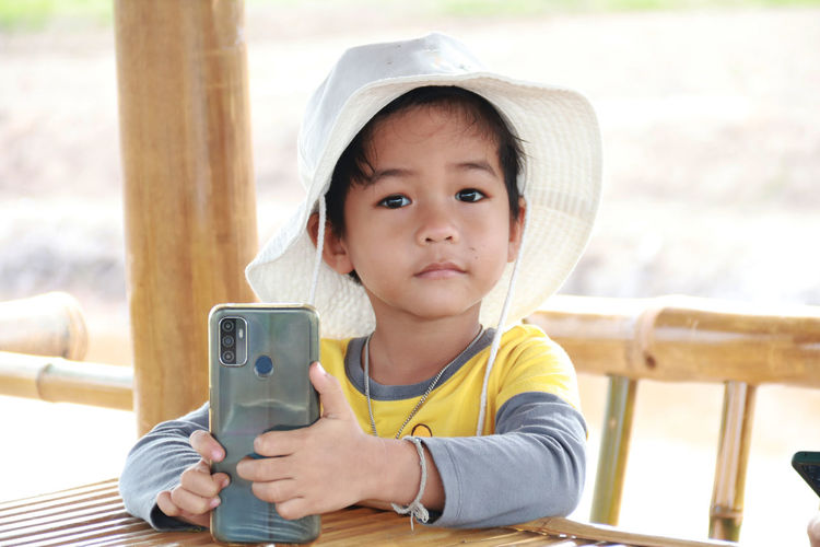Portrait of cute girl using mobile phone at table