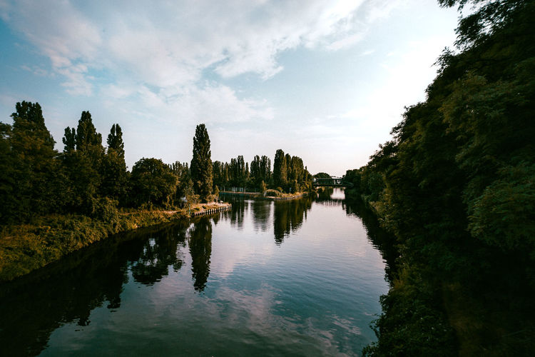 Scenic view of teltow canal amidst trees against sky