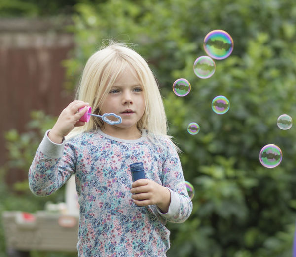 Bubble Bubble Wand Carefree Casual Clothing Childhood Cute Day Elementary Age Focus On Foreground Front View Girls Holding Human Face Innocence Leisure Activity Outdoors Park Person Playful Selective Focus Short Hair Standing
