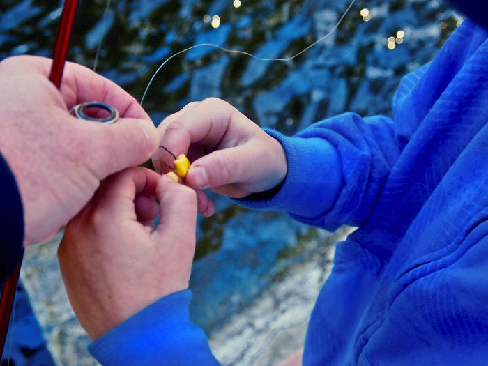 Son helping father in attaching corns to fishing hook