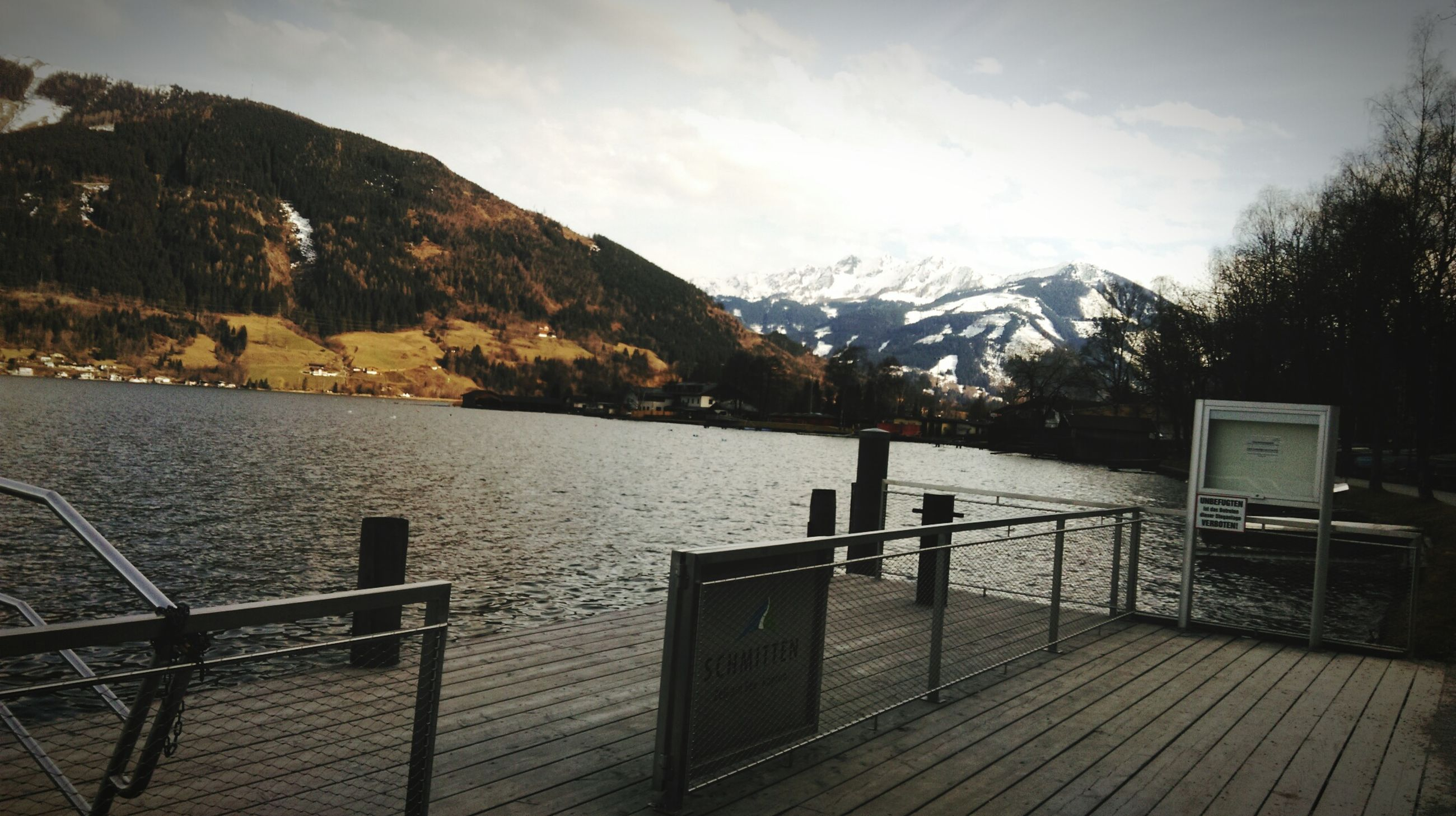 mountain, water, sky, railing, tranquility, tranquil scene, lake, scenics, nature, beauty in nature, cloud - sky, mountain range, tree, pier, built structure, river, bench, cloud, idyllic, outdoors