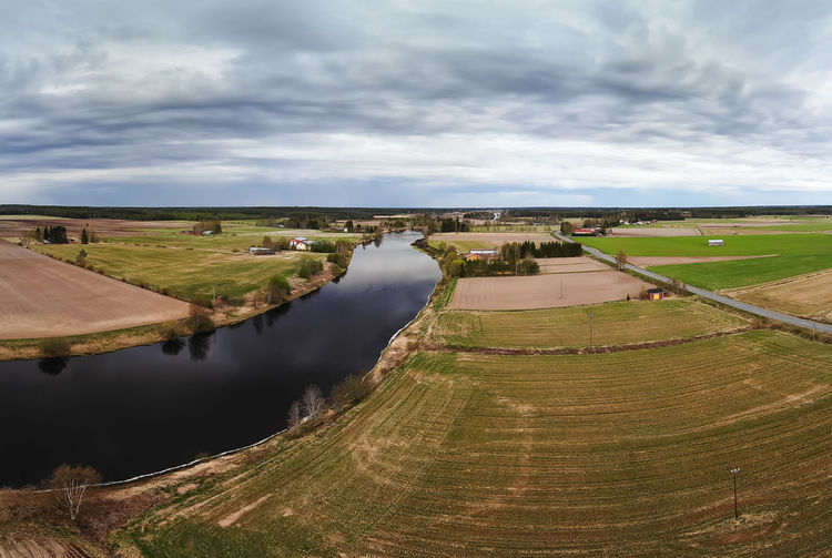 A dramatic cloud formation over the river and fields at the rural finland.