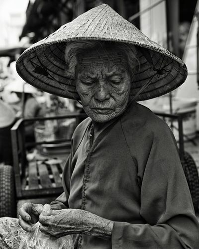 Senior Woman Wearing Asian Style Conical Hat Holding Plastic Bag