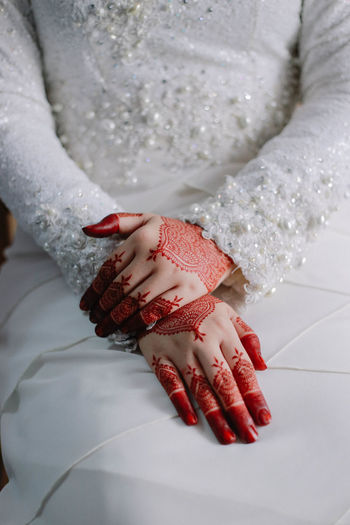Midsection of bride with henna tattoo during wedding ceremony