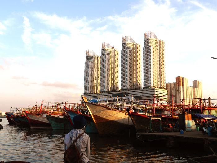 Ship in sea against sky in city