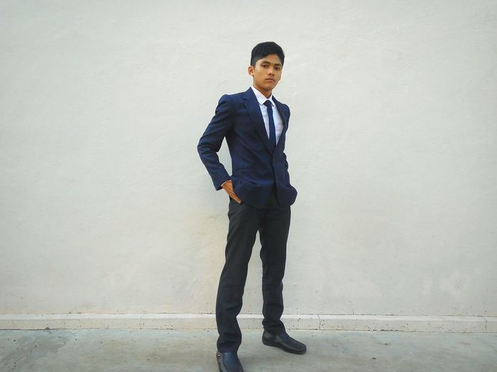 Full length portrait of young businessman standing against wall