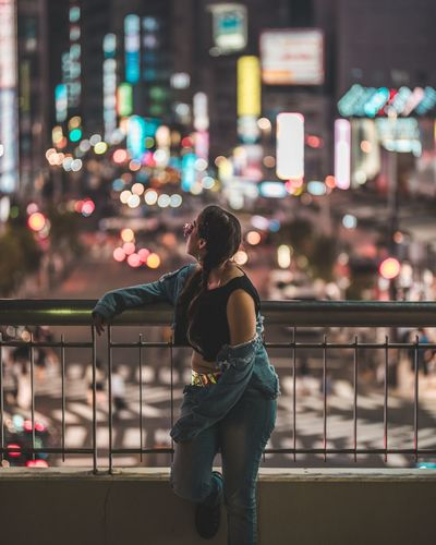 Full length of woman standing against illuminated city at night