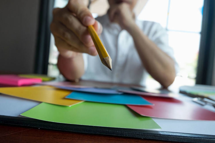 Midsection of design professional with pencil choosing color at desk
