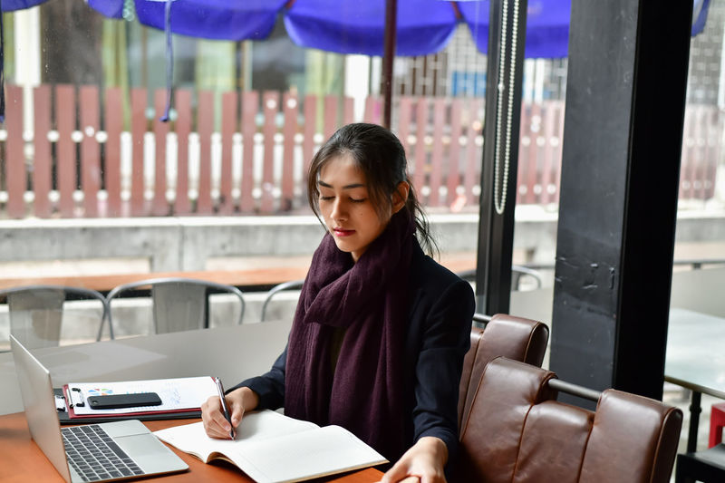 Business Concept.Young Asian businesswoman is working happily.Young businesswoman working in a cafe.Young businesswoman is relaxation in a coffee shop. Adult American Asian  Background Beautiful Beauty Business Businesspeople Businesswoman Cafe Caucasian Chinese Coffee Coffee Shop Coworker Document Education Educational European  Female Happiness Happy Holding Indoor Japan Japanese  Life Lifestyle Market Occupation Office Online  People Personal Professional Relax Relaxation Shop Smiling Student Study Success Successful Team Teamwork Transaction Woman Work Worker Young