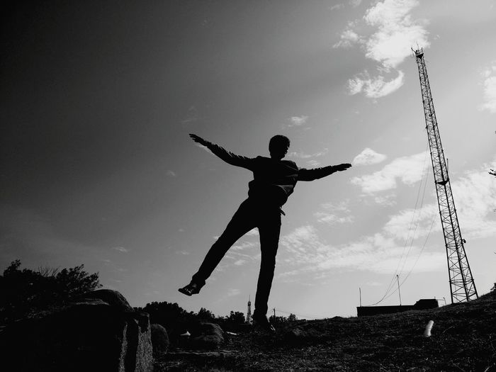 Silhouette Man With Arms Outstretched Posing On Field Against Sky