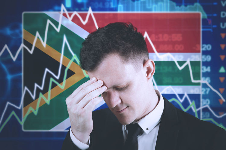 Close-up of stressed businessman touching forehead against flag