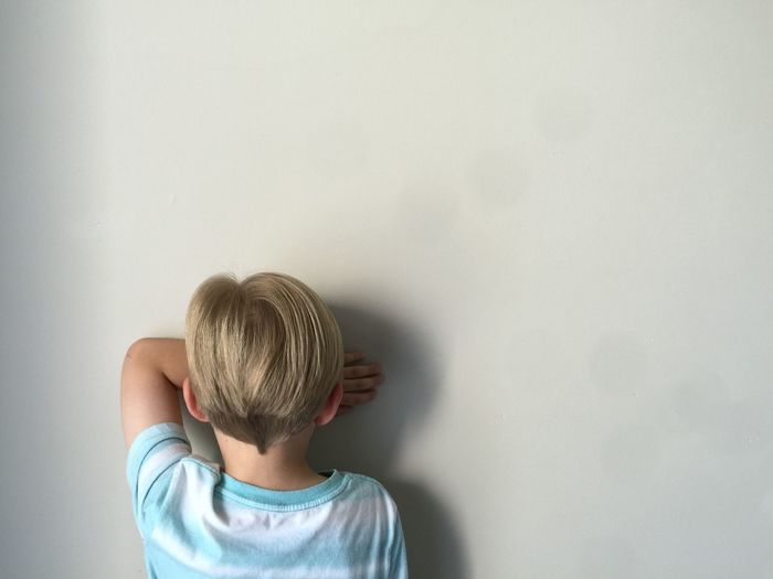 Rear view of boy standing by wall