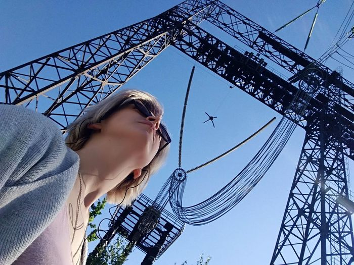 Low angle view of mid adult woman standing against clear blue sky during sunny day