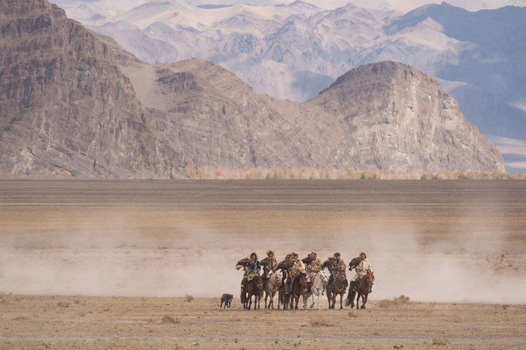 People in desert against mountains