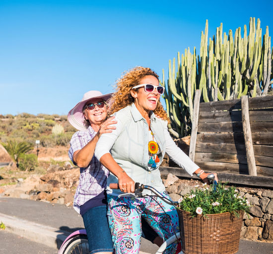 Happy woman with friend riding bicycle on road during sunny day