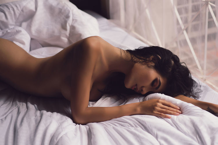 Side View Of Sensuous Naked Female Model Lying On Bed