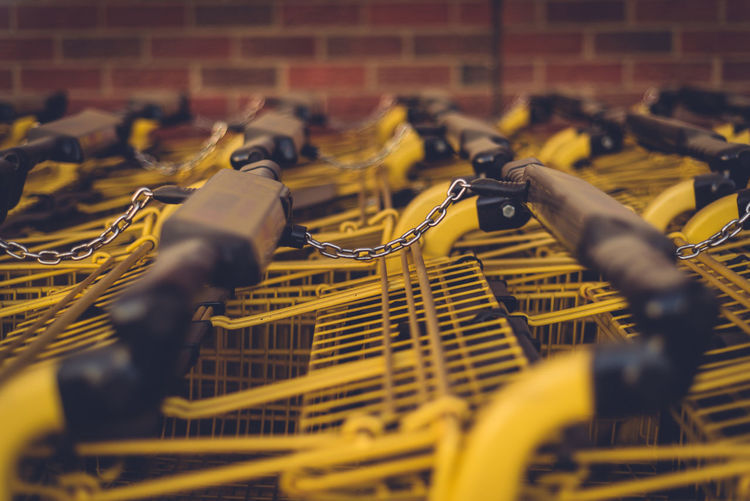 All In A Row Brick Wall Close-up Day Grocery Carts Low Angle View No People Selective Focus Yellow Carts