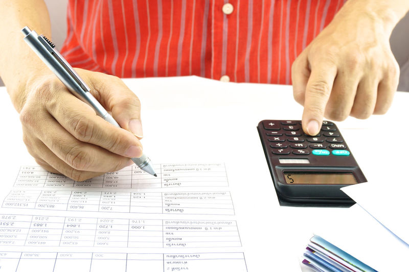 Midsection of man calculating bills on desk