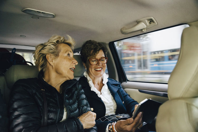 Senior woman talking with friend using mobile phone in car
