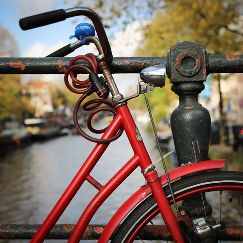 Close-up of bicycle wheel by river in city