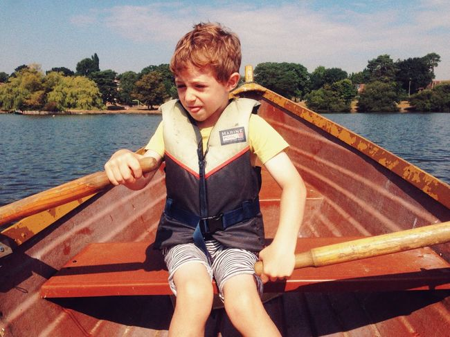 Seven year old boy rowing a boat, Petersfield, Hampshire, England, United Kingdom Sitting Lifestyles One Person Young Adult Water Leisure Activity Nature Day Real People Nautical Vessel Outdoors Sky Tree Boy Seven Years Old Young Boy Rowing