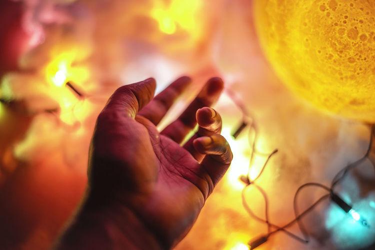 Close-up of hand by illuminated lighting equipment