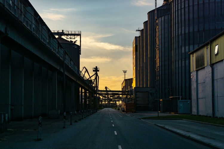 Street and industrial buildings in the port of Rostock during sunset Sky Silo Harbor Building Street Sunset Shipyard Cargo Container Shipping  District Loading Industrial Ship Trucking Loading Dock Distribution Warehouse Crane - Construction Machinery