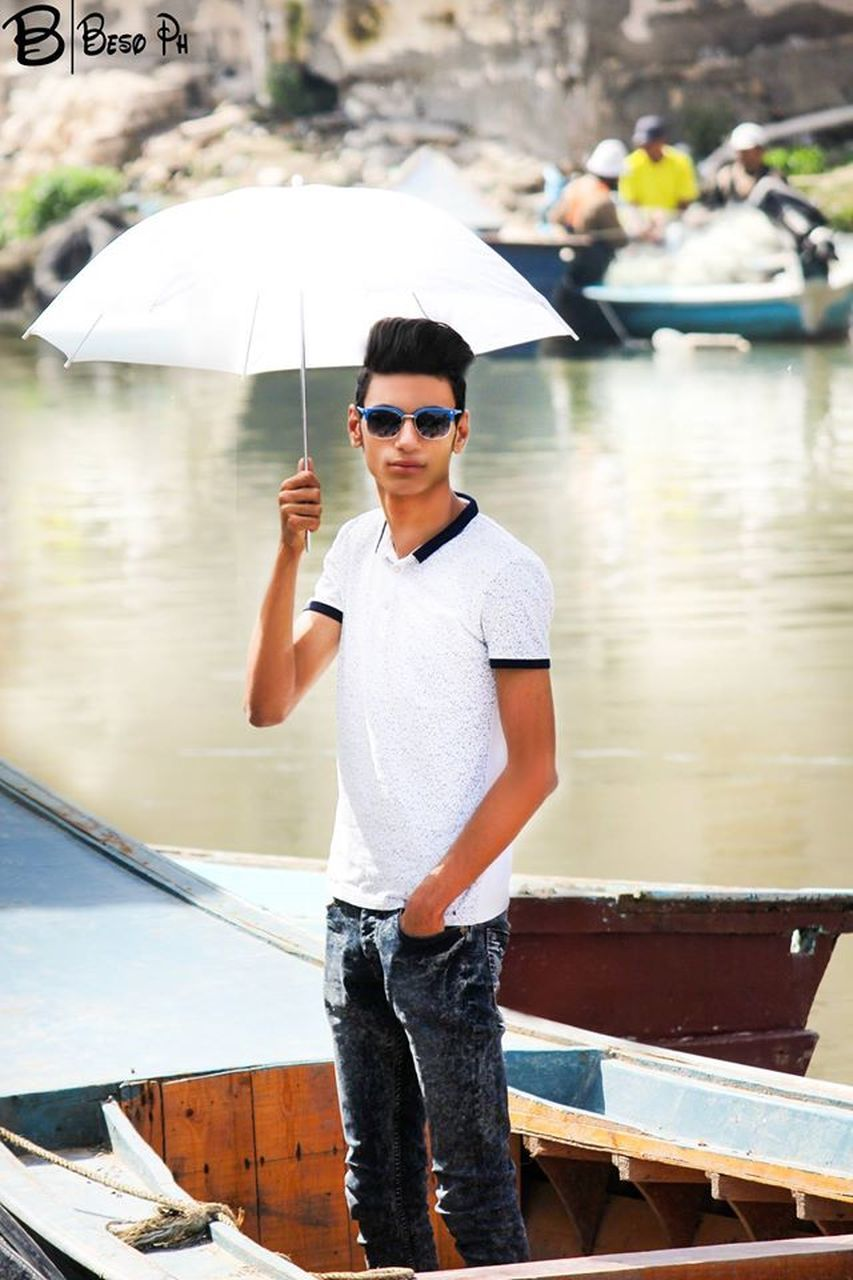 sunglasses, real people, one person, water, nautical vessel, lifestyles, transportation, day, leisure activity, casual clothing, young adult, standing, young men, outdoors, mode of transport, focus on foreground, looking at camera, cap, portrait, nature, young women