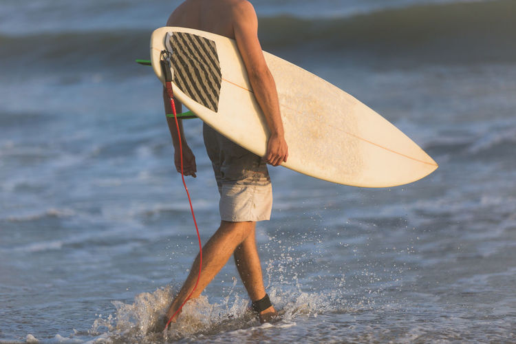 Low section of man holding surfboard while walking on shore at beach