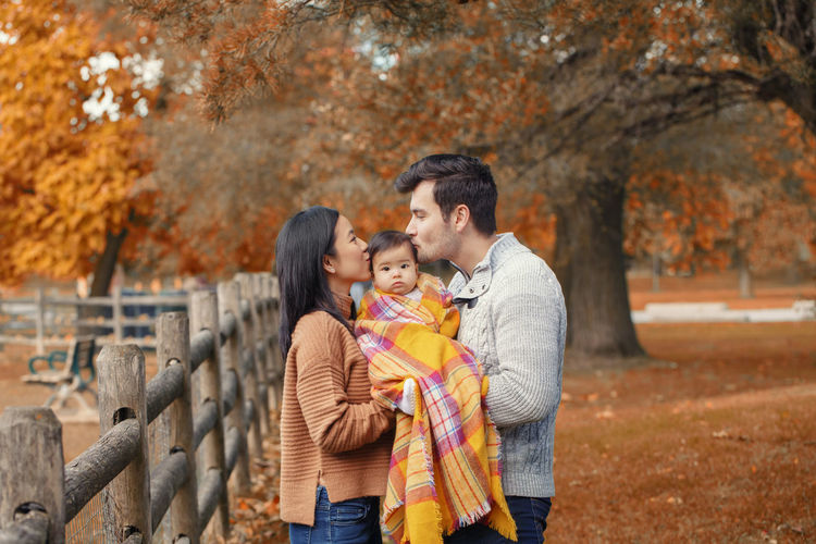 Parents kissing toddler in park during autumn