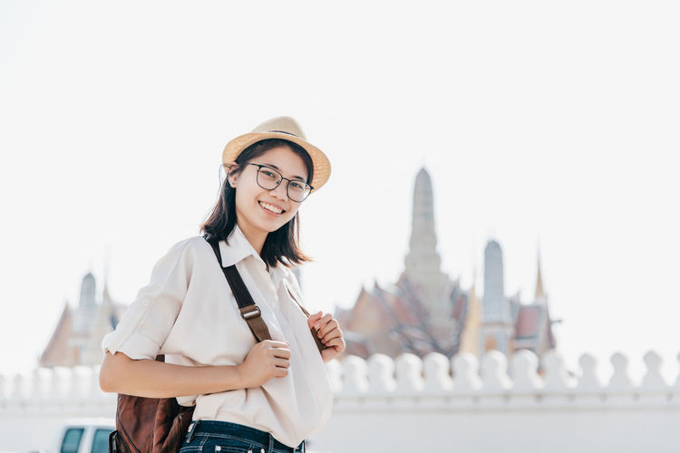 Portrait of smiling young woman standing against clear sky