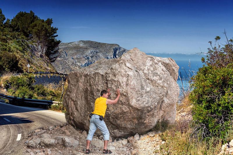 Rear view full length of man pushing boulder rock