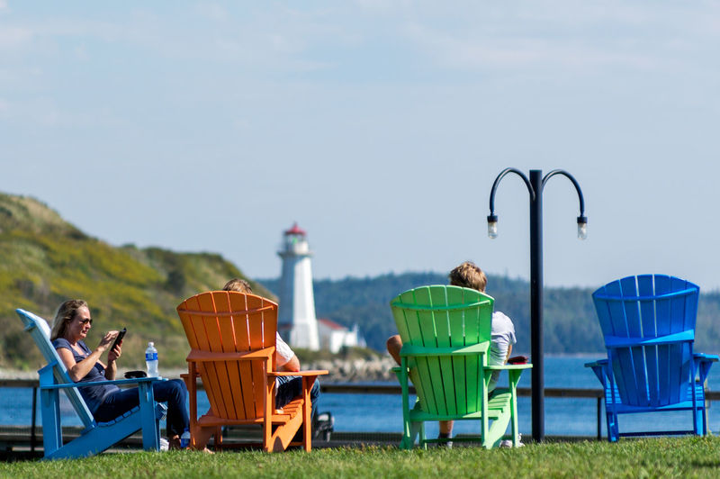 Taking it Easy Adirondack Chairs Architecture Blue Sky Building Exterior Built Structure Colourful Day Field Grass L Landscape Leisure Activity Lifestyles Nature Outdoors Person Protection Rear View Relaxation Safety Sitting Sky Women