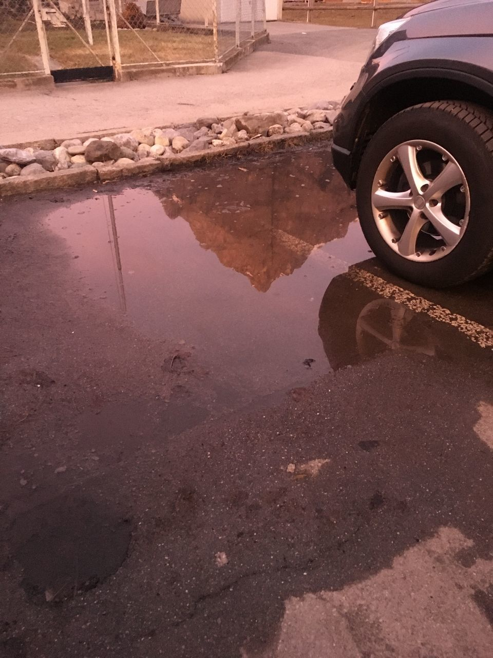 REFLECTION OF ROAD IN PUDDLE ON STREET