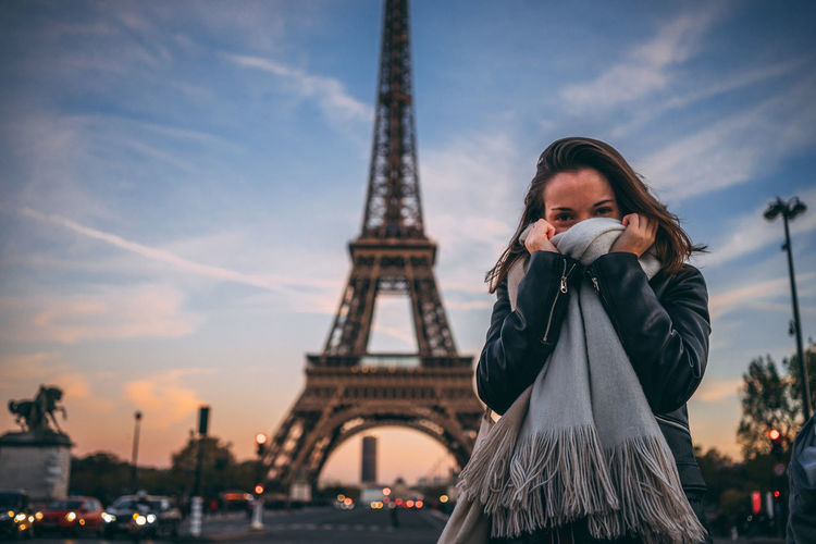 Portrait of woman standing with eiffel tower in background