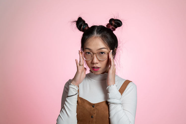 Portrait of young woman wearing eyeglasses against pink background