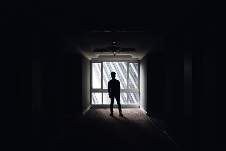 Silhouette Man Standing In Dark Corridor Against Window