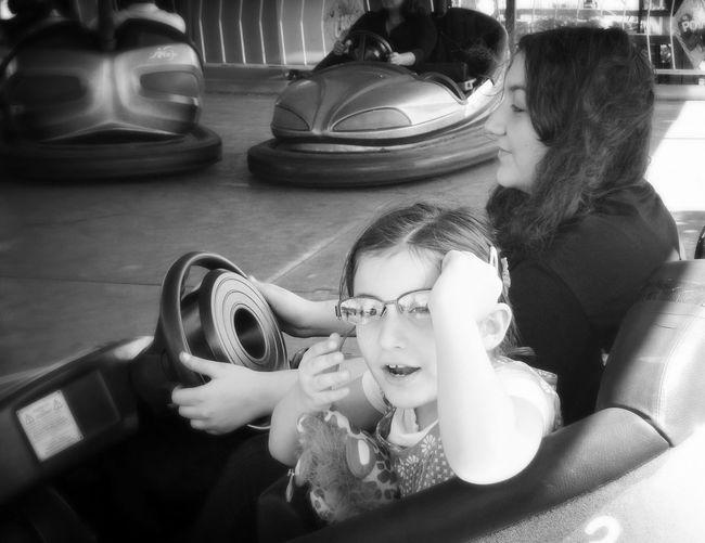 Woman And Daughter Riding Bumper Car At Amusement Park