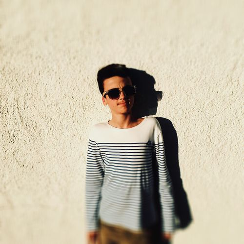 Portrait Of Boy In Sunglasses Standing Against Wall