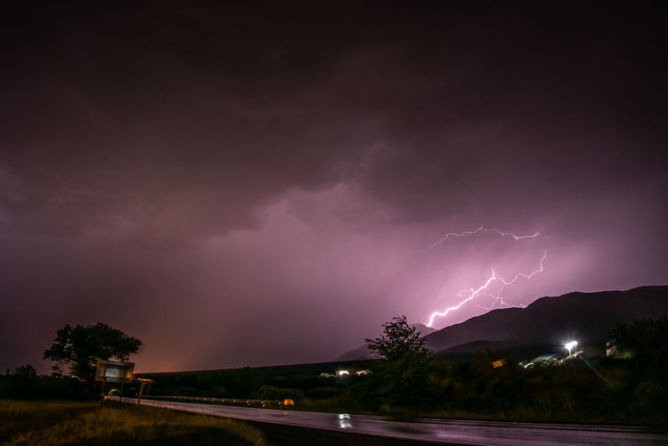 Power In Nature Night Beauty In Nature Cloud - Sky Lightning Storm Power Sky No People Thunderstorm Nature Illuminated Sign Storm Cloud Warning Sign Scenics - Nature Communication Environment Mountain Outdoors Ominous Purple