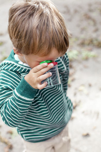 High angle view of boy looking through bottle