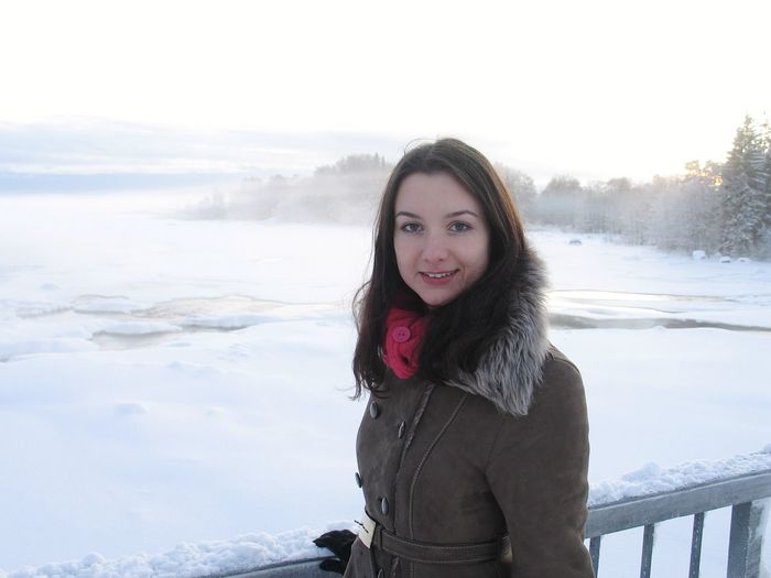Portrait of smiling young woman standing by railing during winter