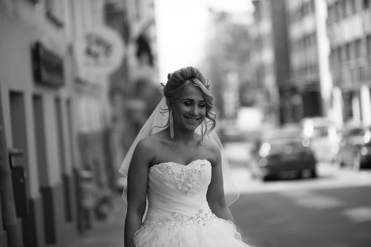 portrait of bride Architecture Authentic Moments Beautiful Woman Black & White Blckandwhite Bride Candid Celebration Day Focus On Foreground Front View Happiness Happy People Life Events One Person Outdoors People Real People Smiling Standing Street Wedding Wedding Dress Young Adult Young Women