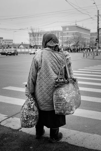 Rear view of woman with bags standing on street