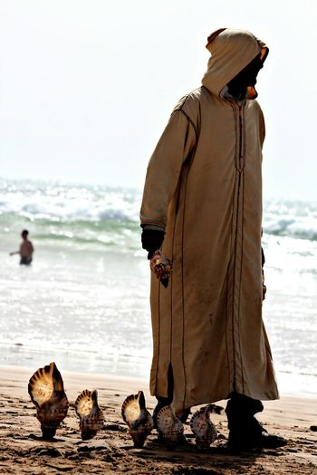 Full Length Of Man With Seashells Standing At Beach